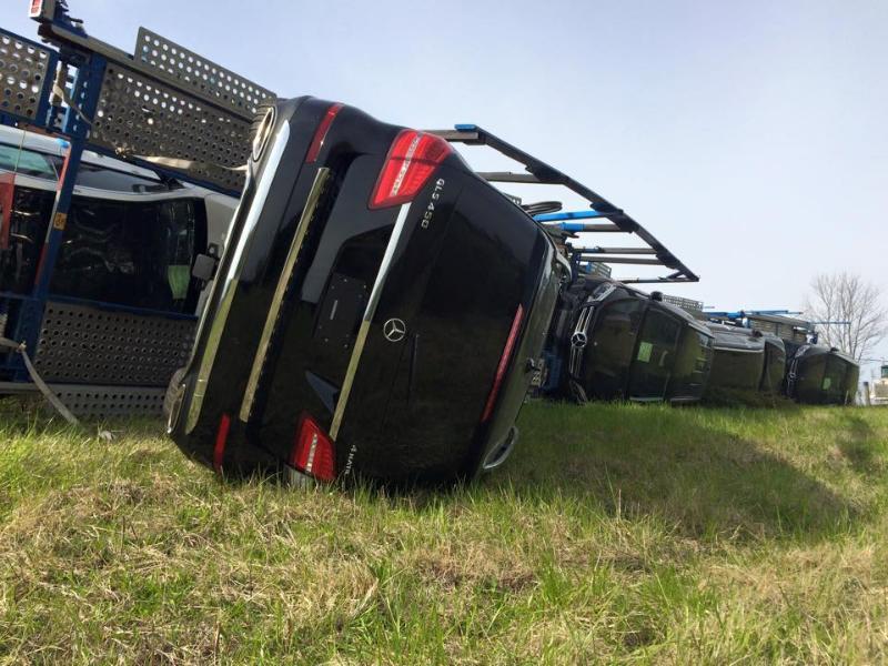 Truck full of Mercedes-Benz cars rolls over