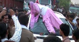 Indian woman climbs on top of a Mercedes SUV after security guard winks at her